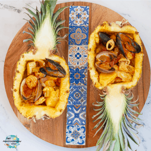 filled pineapple with seafood over round wooden plate