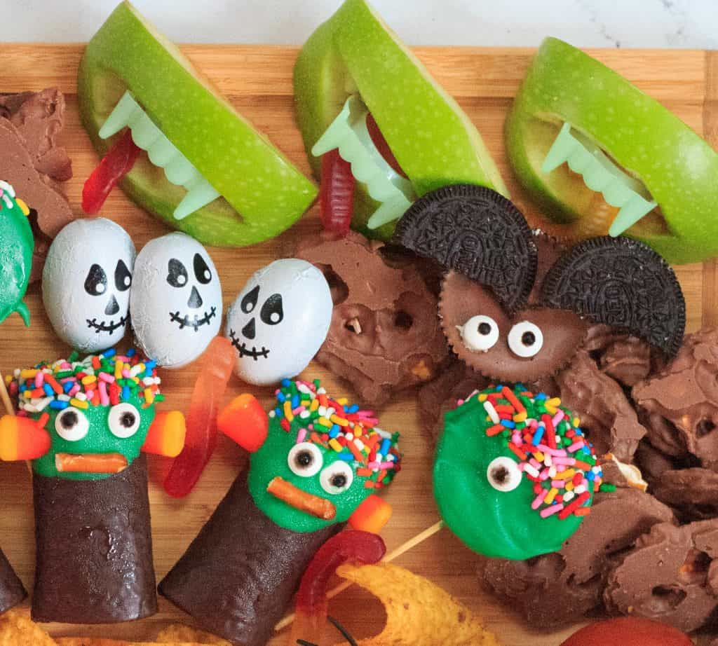 different halloween candies on a wooden board