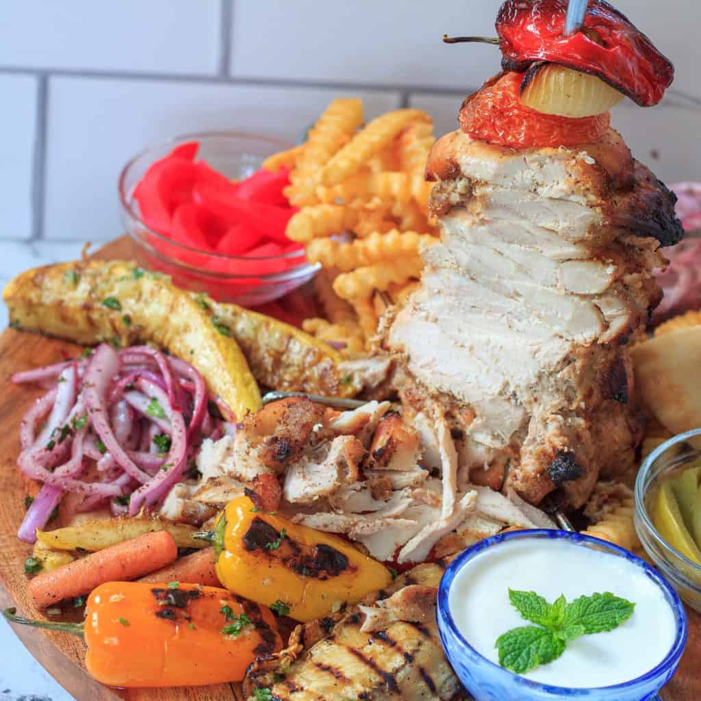 half sliced chicken shawarma skewer on a wooden platter with vegetables and sauces around