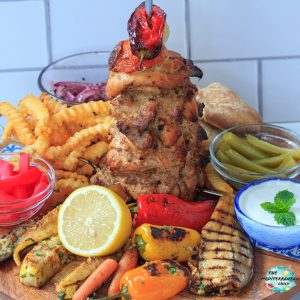 cooked chicken shawarma skewer on a wooden platter with vegetables and sauces around